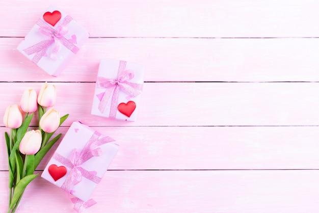 国際女性の日コンセプト。ピンクのチューリップとギフト用の箱と赤いハート