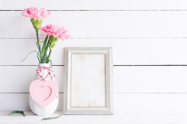 バレンタインの日、愛の概念。古いビンテージ写真フレームと花瓶にピンクのカーネーションの花