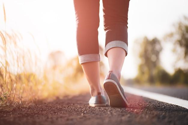 クローズアップ女性が道端に向かって歩きます。ステップの概念