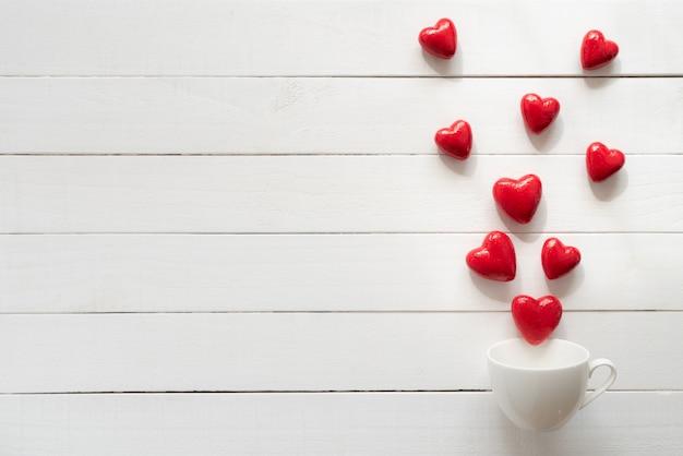 バレンタインの日と愛の概念。赤いハートが白いコーヒーカップからはねかける