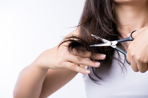 健康的なコンセプトです。女性の手持ち株はさみと彼女の破損した長い髪をカット