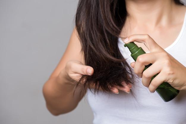 健康的なコンセプトです。オイルヘアトリートメントで破損した長い髪を持つ女性の手
