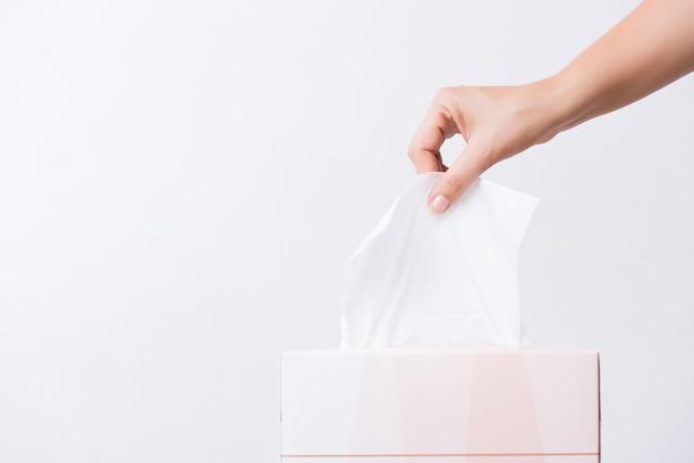 ヘルスケアの概念ボックスから白いティッシュペーパーを選ぶ女性手。