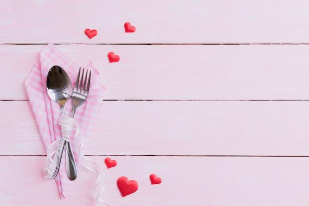 ピンクの木製の背景にバレンタインの日と愛の概念。