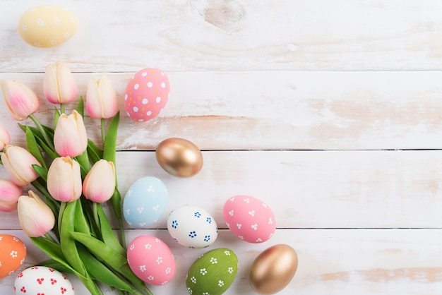 イースター、おめでとう!ピンクのチューリップの花と巣のイースターエッグのカラフルです