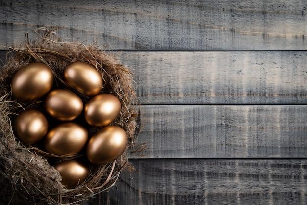 イースターエッグの黄金の巣と羽の木製の背景。