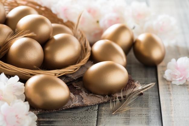 Золотые пасхальные яйца в гнезде с розовым цветком и пером