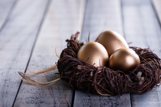 イースター、おめでとう!イースターエッグの黄金の巣と羽の木製の背景