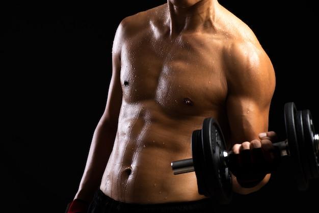 ダンベルで強度のフィットネス体。ボディビルダーと筋肉の概念。