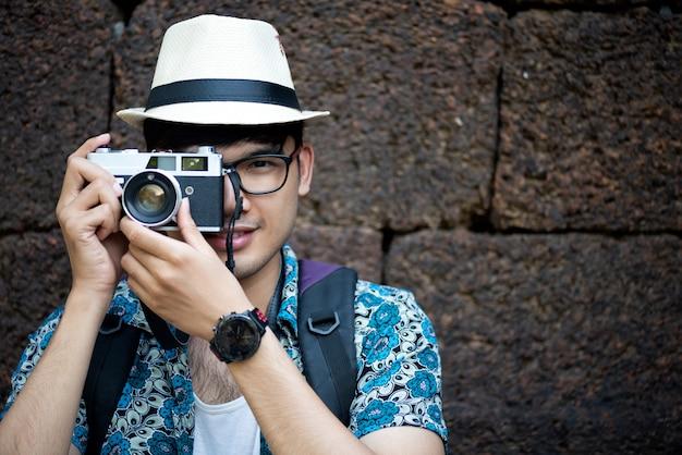 彼のカメラで写真を撮るバックパックを持つ若い男写真家旅行者