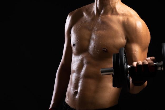 ダンベルで強度のフィットネス体。ボディービルダーと筋肉の概念。