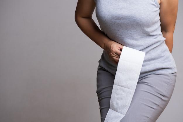 Рука женщины держа ее дно и рулон ткани или туалетной бумаги.
