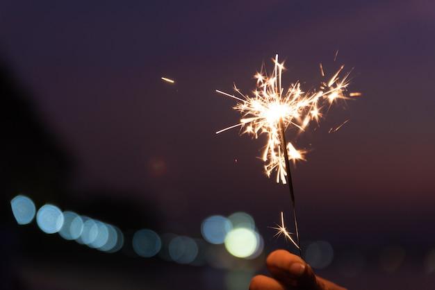 日没時にビーチで線香花火を持っている手。お祝いのコンセプトです。