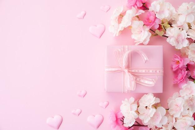 幸せな母の日の概念。紙のハートとギフトボックスとピンクの花