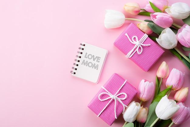 幸せな母の日の概念。ピンクのチューリップ、ラブママテキスト付きギフトボックスのトップビュー
