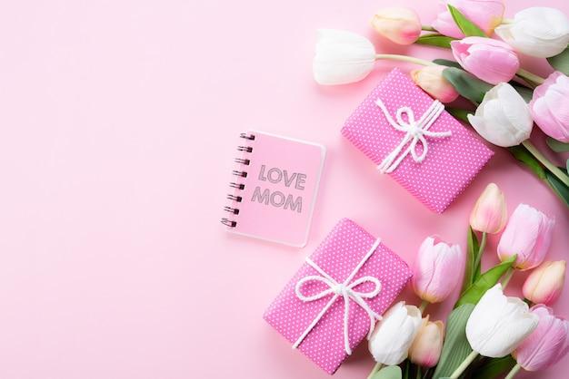 幸せな母の日の概念。ピンクのチューリップの花、ギフト用の箱の上から見る