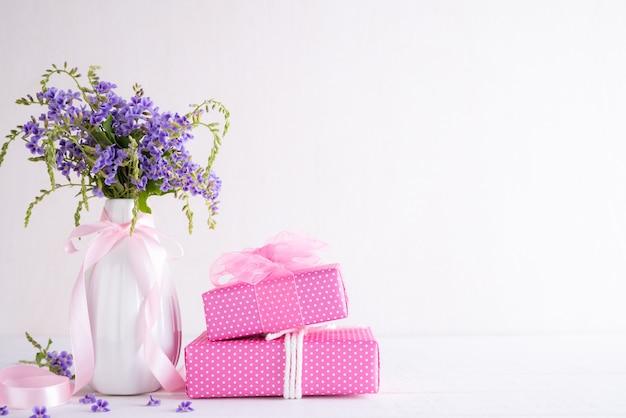 幸せな母の日の概念。白い木製のテーブルの上の紫色の花とギフトボックス