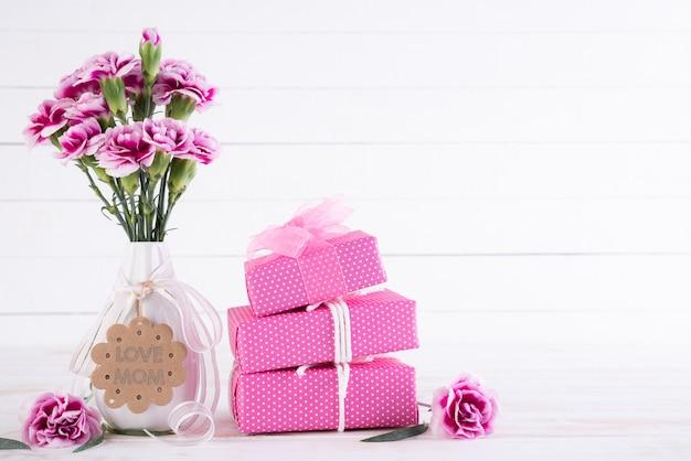 幸せな母の日の概念。ピンクのカーネーションの花とギフトボックス