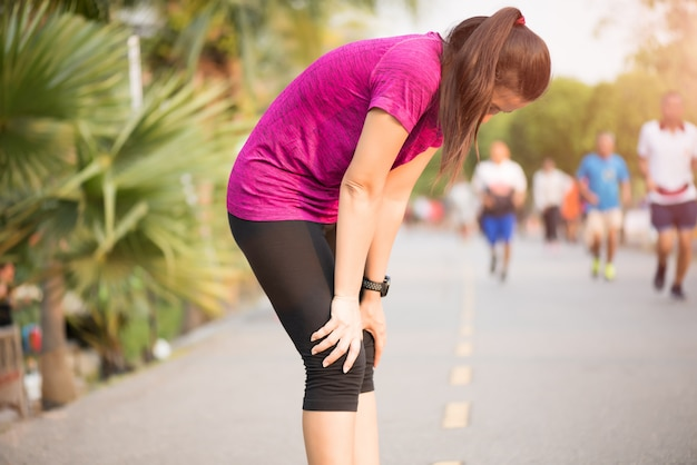 公園でジョギングした後疲れスポーツ少女。スポーツと健康管理の概念。