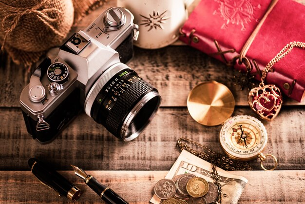 ビンテージの赤い本、コインお金、コンパス、ウッドの背景のレトロな写真フィルムカメラ。