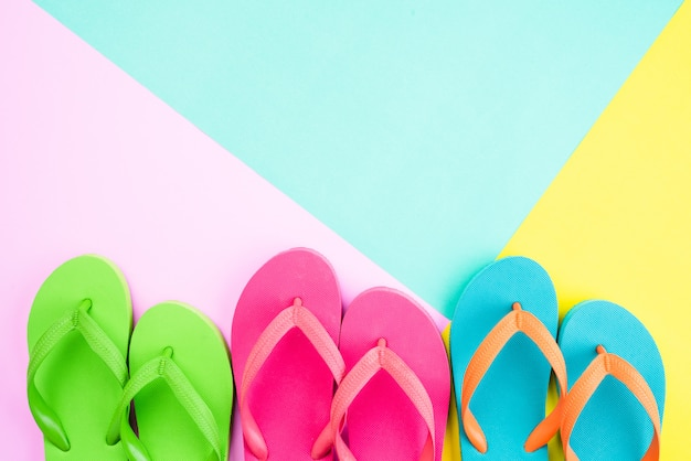 夏の休日のためのピンクと黄色の背景にカラフルなフリップフロップのトップビュー
