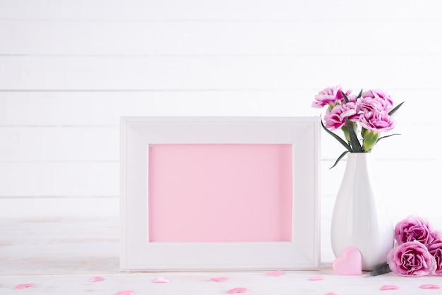 白い木製のテーブルの上に花瓶に素敵なピンクのカーネーションの花と白の写真フレーム