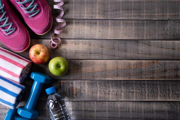 暗い背景の木のテーブルに運動選手の装備の平面図です。健康的なライフスタイルのコンセプト