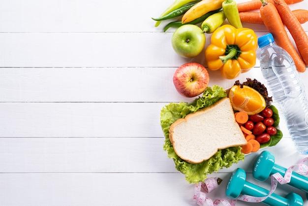 Здоровая концепция образа жизни, еды и спорта на белой деревянной предпосылке.