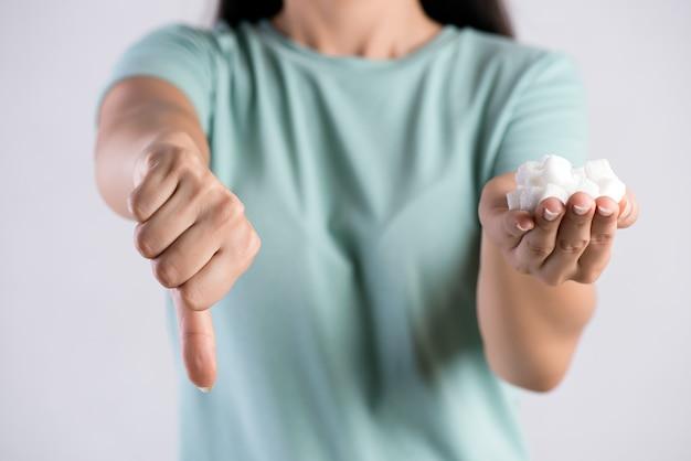 Женщина руки, держа кубики белого сахара с большими пальцами руки вниз
