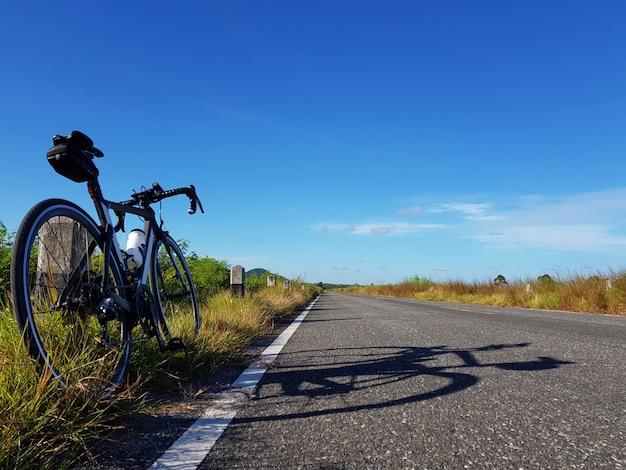 Велосипед припаркованный около открытой дороги с голубым небом. концепция свободы и транспорта.