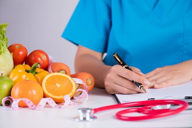 健康的なライフスタイル、医者の机の上の食べ物と栄養の概念。