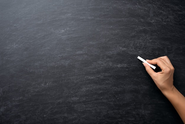 教育や学校に戻るコンセプト。黒板にチョークを持っている手。
