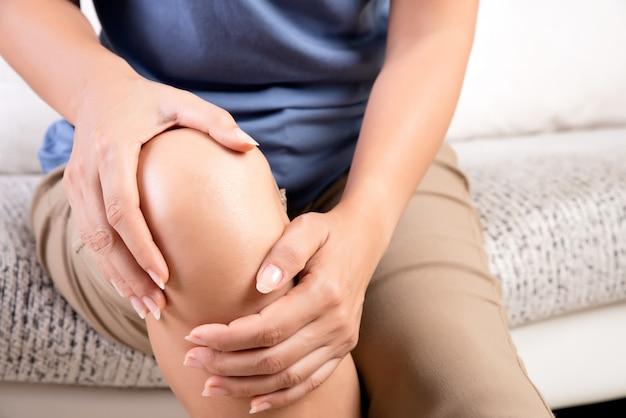 Женщина сидя на софе и чувствуя боль колена, здравоохранение и медицинскую концепцию.