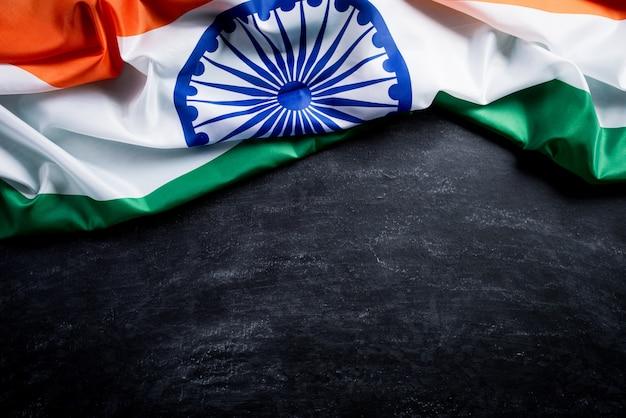 Национальный флаг индии на фоне доски. день независимости индии.