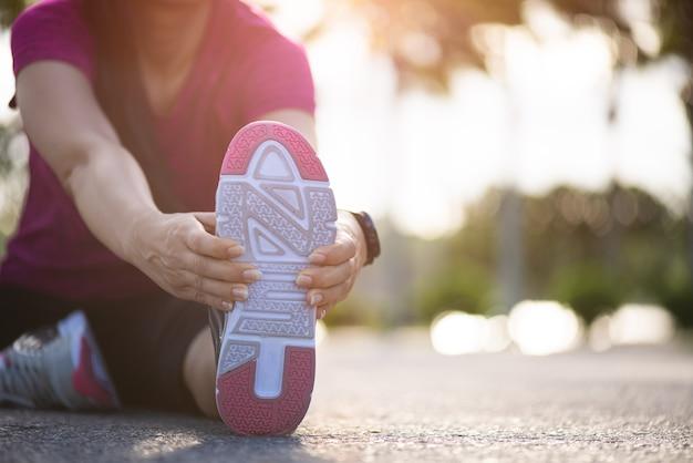 公園で実行する前に足を伸ばして道路に座っている女性ランナー。