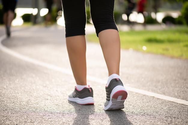 道路側に向かって歩いている女性。ステップ、散歩、屋外運動のコンセプト。