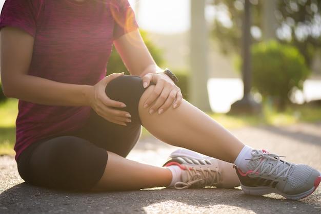 女性ランナーは、公園で膝に痛みを感じます。屋外運動のコンセプト。