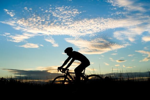 Силуэт велосипедиста, езда на дорожном велосипеде по открытой дороге вечером во время заката