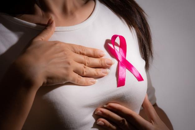 乳がんをサポートするために女性の胸にピンクのバッジリボン。健康管理。