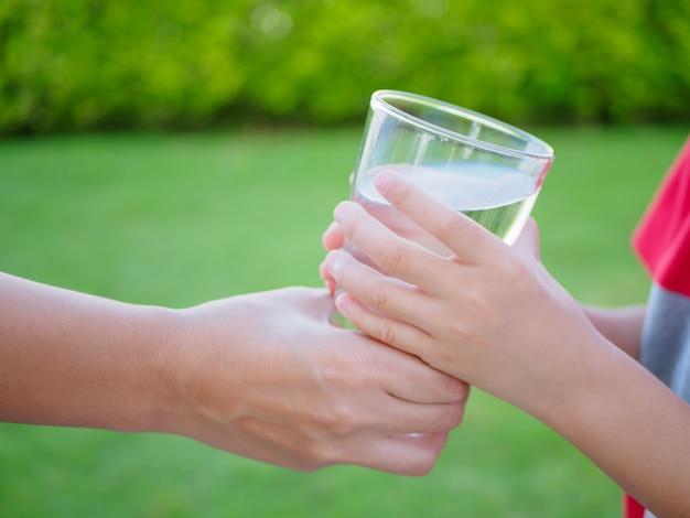 緑の草の背景に子供に水のガラスを与える女性の手。