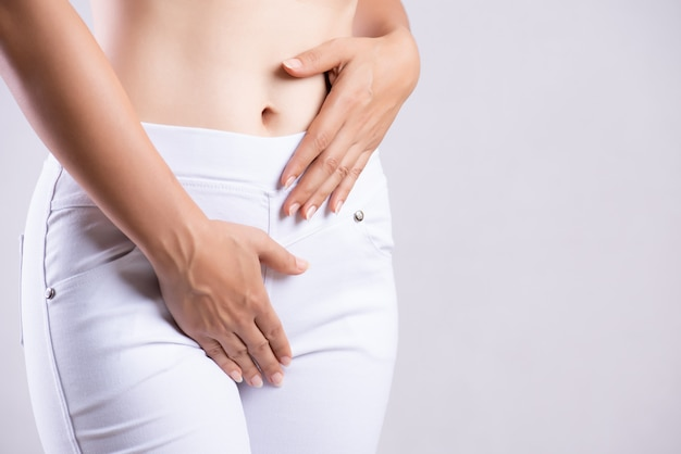 彼女の股の下腹部を押すと両手で痛みを伴う腹痛を持つ女性
