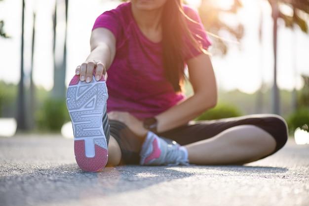 Женщина-бегун сидит на дороге, разминает ноги перед бегом в парке.