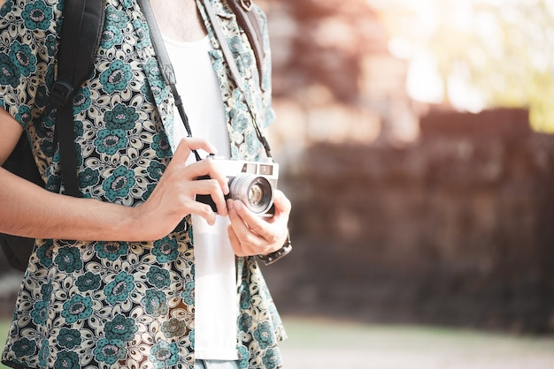 写真を撮るバックパックと若い男の写真家旅行者