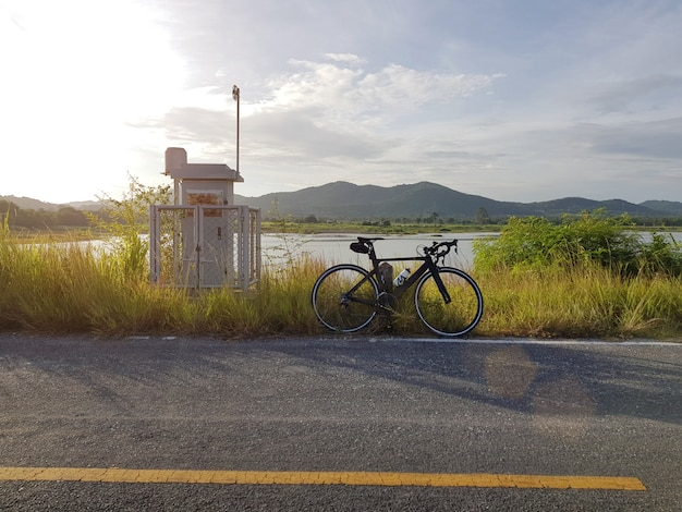 Велосипед на стоянке возле открытой дороги с голубым небом