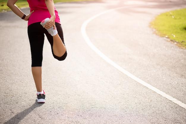Бегун вытягивает ноги перед бегом в парке.