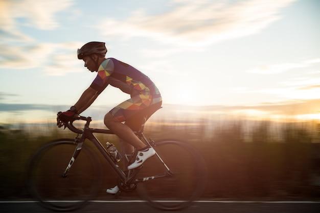 朝、スポーツコンセプトの男サイクリングロードバイク