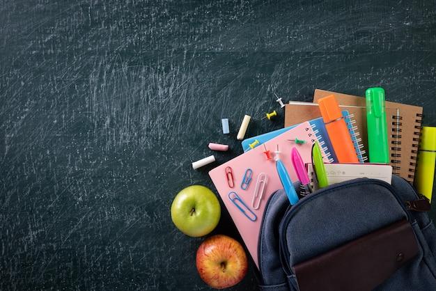 学校のバックパックと黒板の背景を持つ学用品