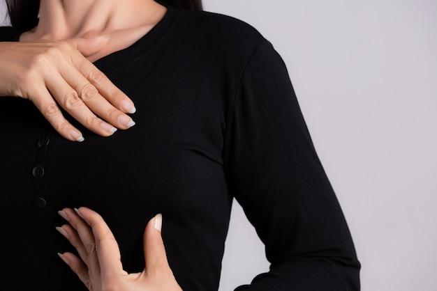 女性の手が乳がんの兆候のために彼女の胸のしこりをチェック