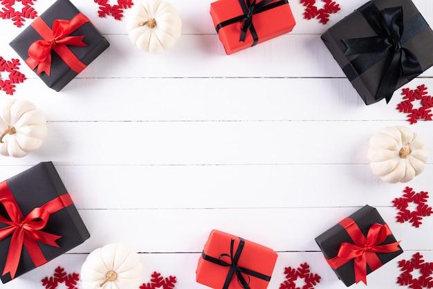 白い木製の背景の赤と黒のクリスマスボックス。ブラックフライデー。