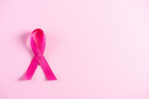 乳がんの意識をサポートするためのピンクの紙の背景にピンクのリボン